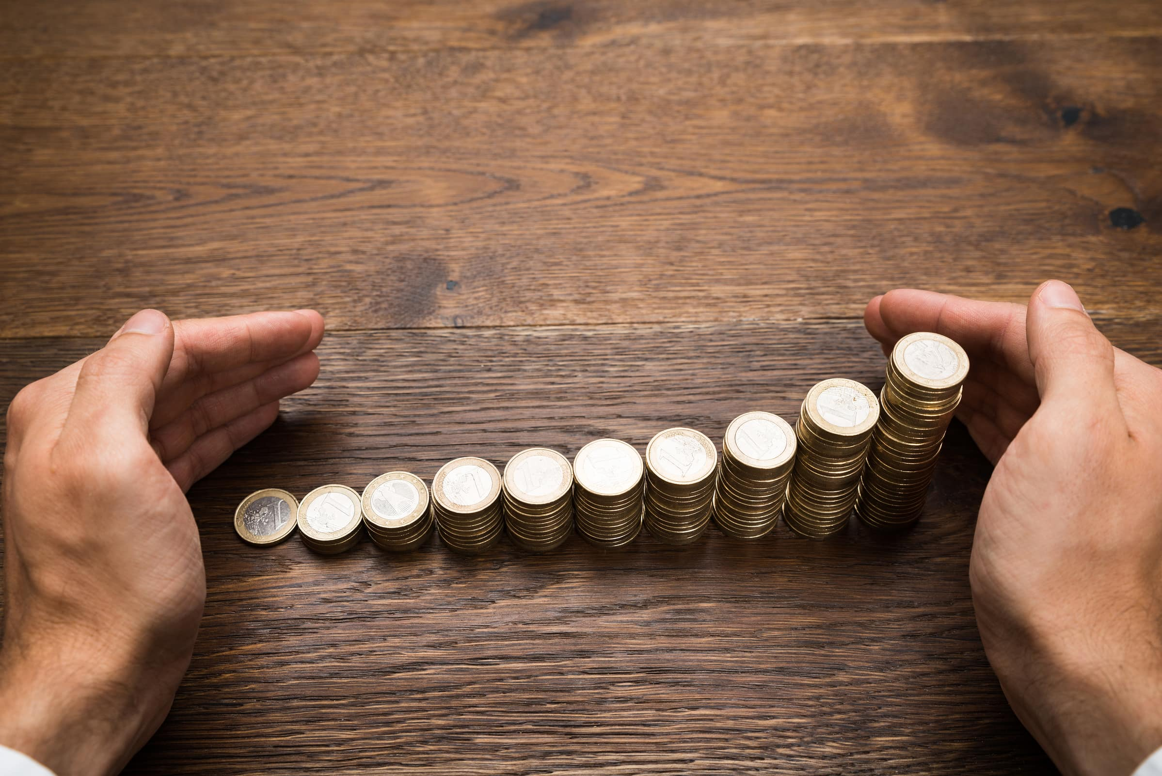 Close-up Of A Businessman's Hand Protecting Stack Of Coins