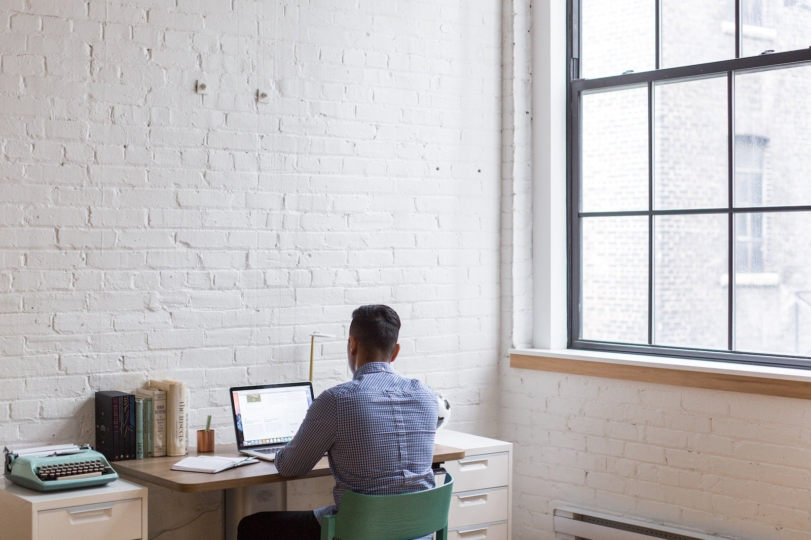 person sitting and working remotely at a desk