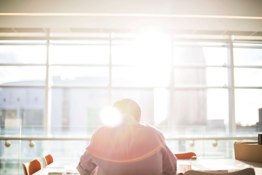 Man sitting in an office with sunshine coming through the window.