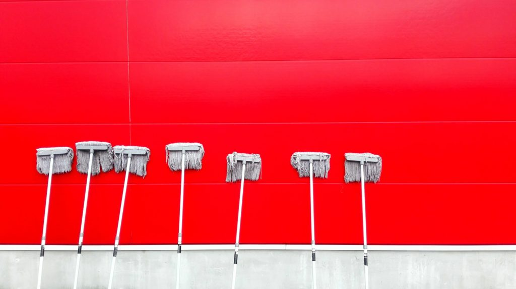 White mops leaning up against a bright red wall